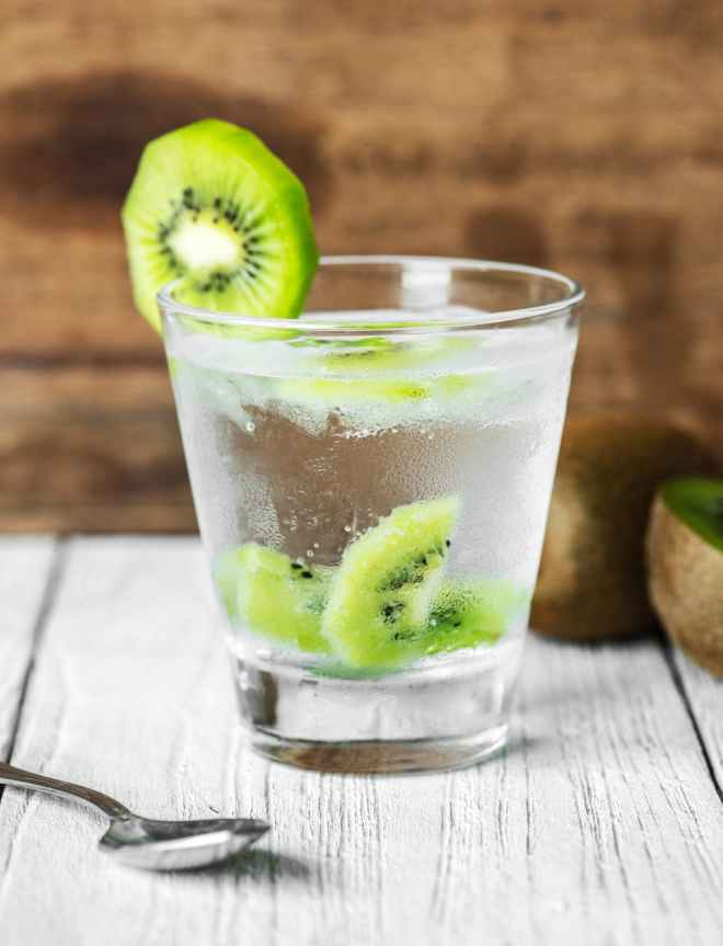 clear drinking glass filled with clear liquid and sliced of kiwi